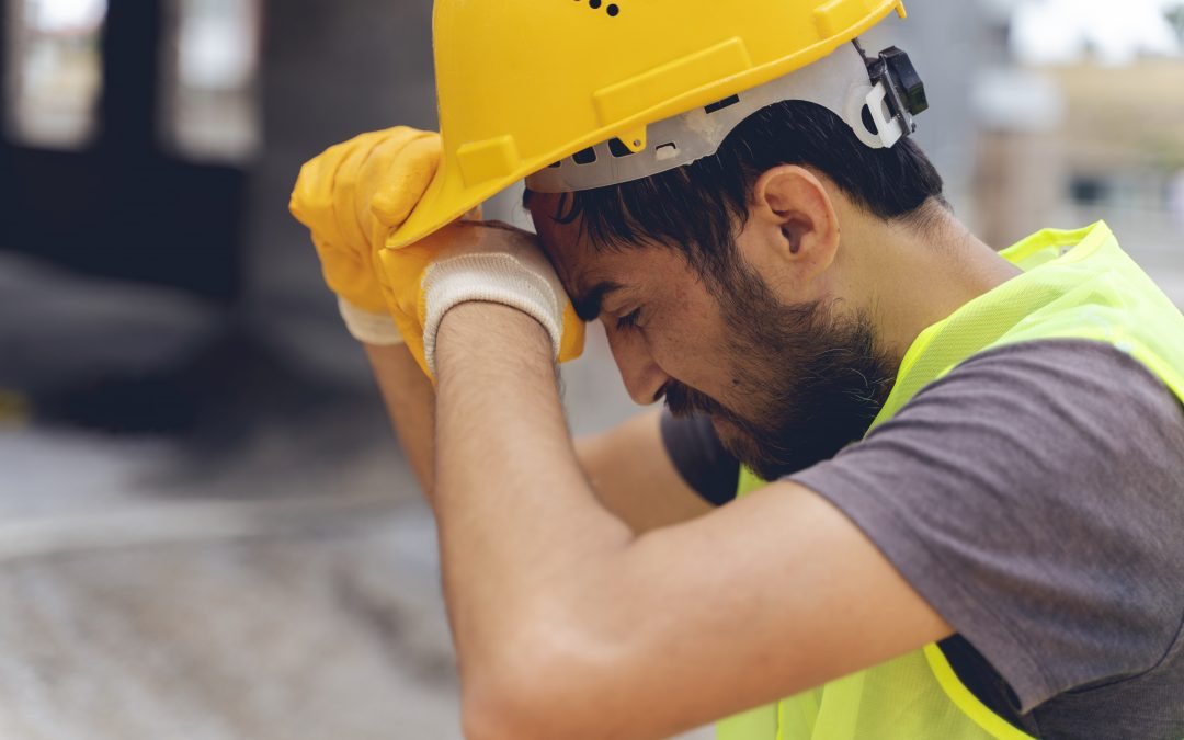 A tired construction worker wiped his head